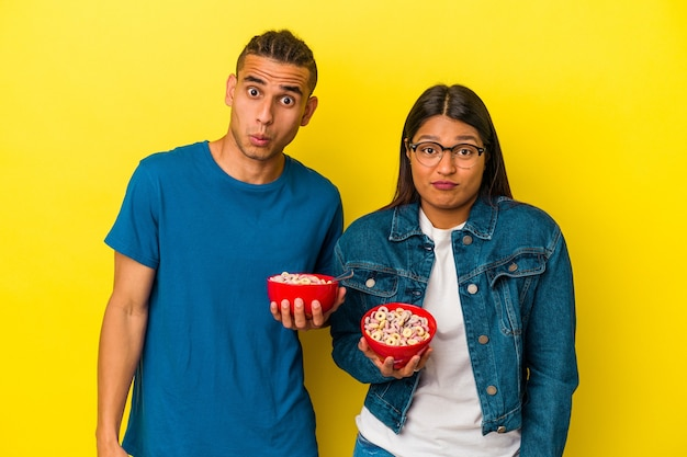 Young latin couple holding a cereals bowl isolated on yellow background shrugs shoulders and open eyes confused.