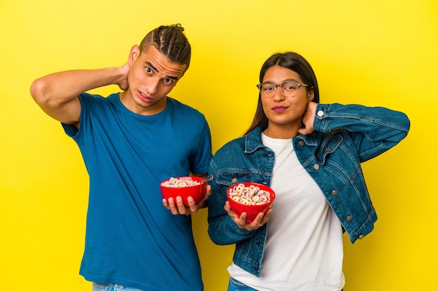 Young latin couple holding a cereals bowl isolated on yellow wall touching back of head, thinking and making a choice.