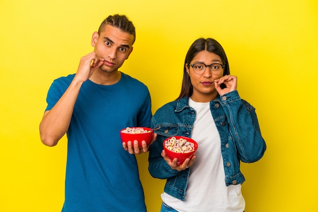 Young latin couple holding a cereals bowl isolated on yellow wall with fingers on lips keeping a secret.