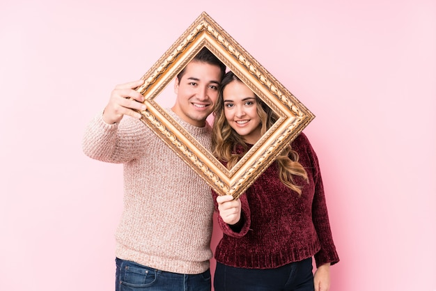 Young latin couple holding a frame