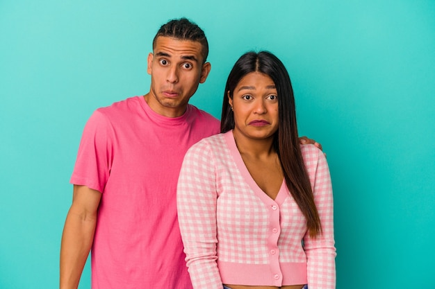 Young latin couple isolated on blue background shrugs shoulders and open eyes confused.