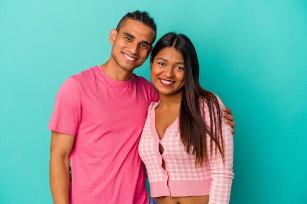 若いラテンカップルは、幸せ、笑顔、陽気な青い背景で隔離。