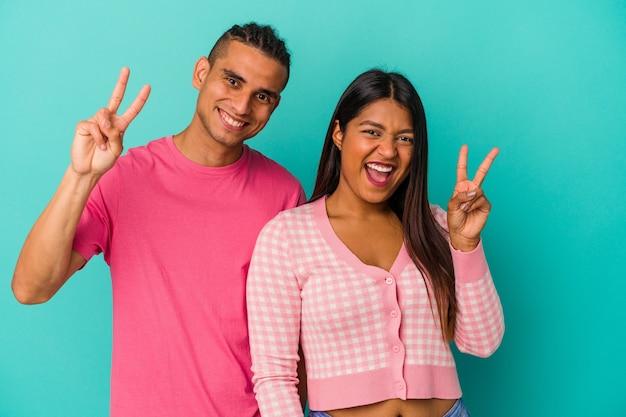 青の背景に孤立した若いラテンカップルは、指で平和のシンボルを示して楽しくてのんき。