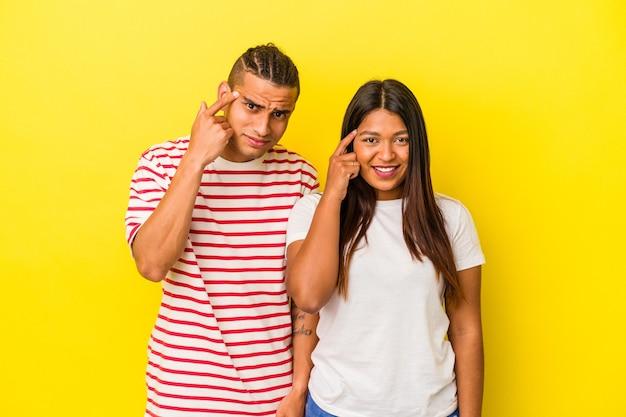 人差し指で失望のジェスチャーを示す黄色の背景に分離された若いラテンカップル。