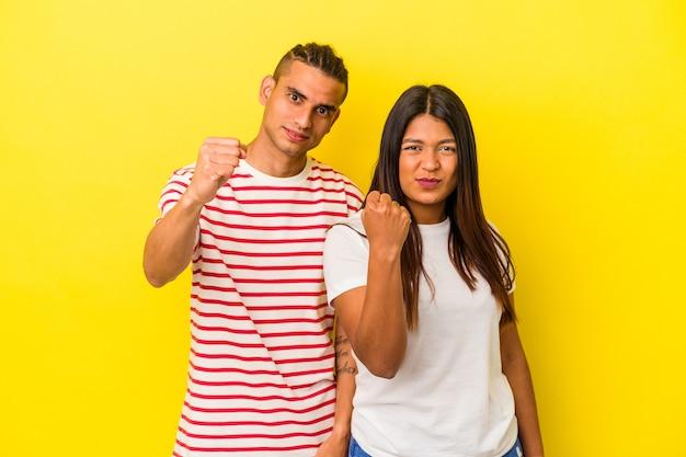 カメラに拳、攻撃的な表情を示す黄色の背景に分離された若いラテンカップル。
