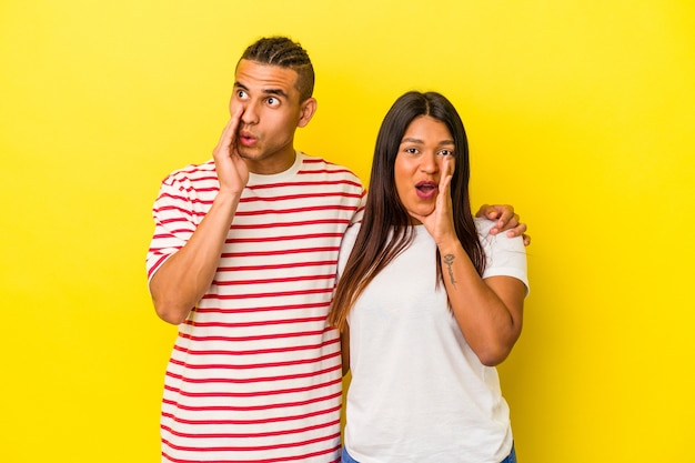 Young latin couple isolated on yellow background is saying a secret hot braking news and looking aside