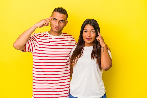 Young latin couple isolated on yellow background pointing temple with finger, thinking, focused on a task.