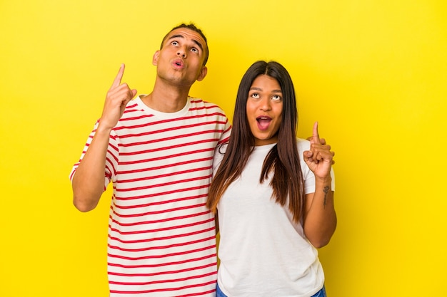 Young latin couple isolated on yellow background pointing upside with opened mouth.