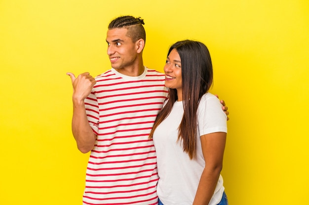 Young latin couple isolated on yellow background points with thumb finger away, laughing and carefree.