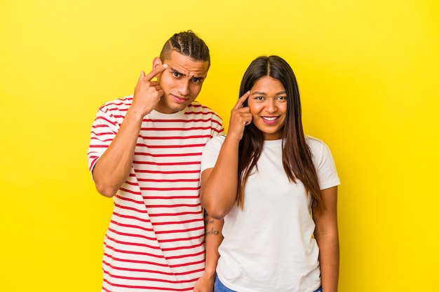 Young latin couple isolated on yellow background showing a disappointment gesture with forefinger.