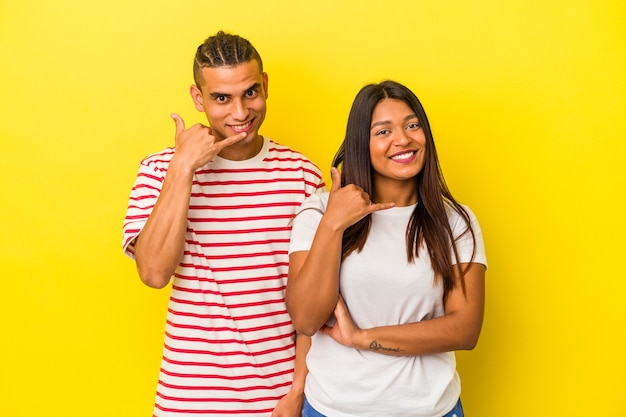Young latin couple isolated on yellow background showing a mobile phone call gesture with fingers.