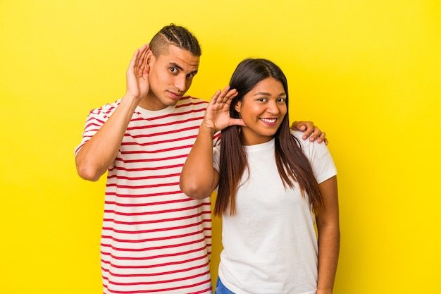 Young latin couple isolated on yellow background trying to listening a gossip.