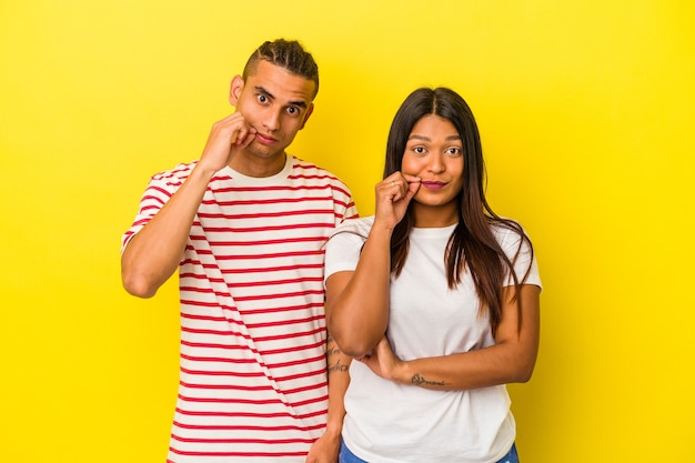 Young latin couple isolated on yellow background with fingers on lips keeping a secret.