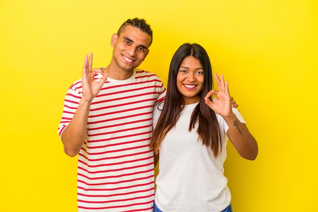 Young latin couple isolated on yellow wall cheerful and confident showing ok gesture.