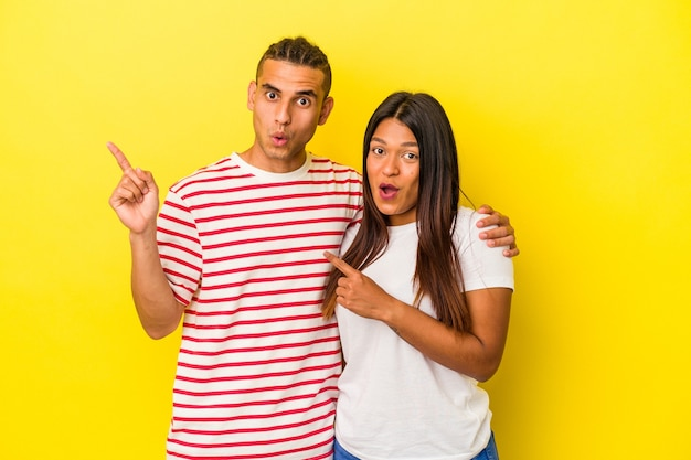 Young latin couple isolated on yellow wall pointing to the side