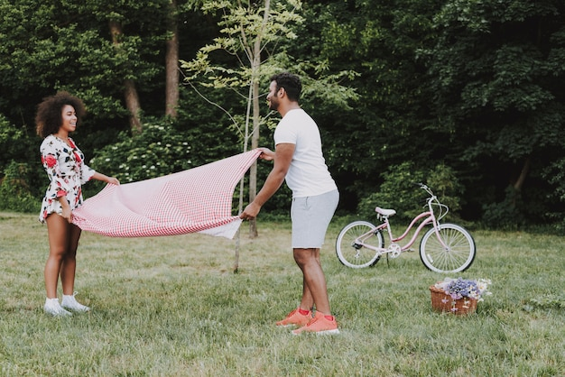 Young latin couple lay tablecloth for picnic