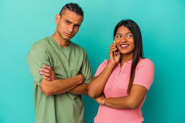 青い背景で隔離の携帯電話と若いラテンカップル