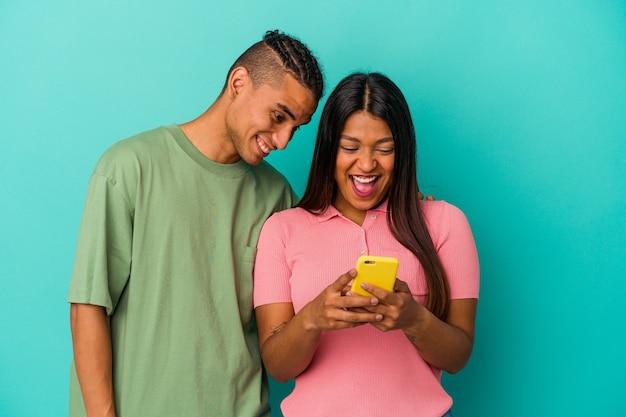 Молодая латинская пара с мобильным телефоном на синем фоне