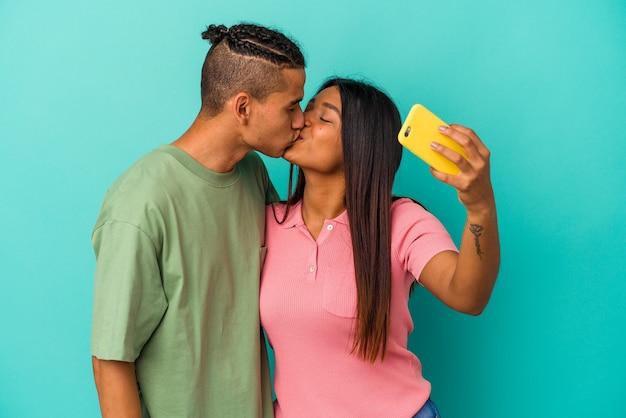 Молодая латинская пара с мобильным телефоном на синей стене