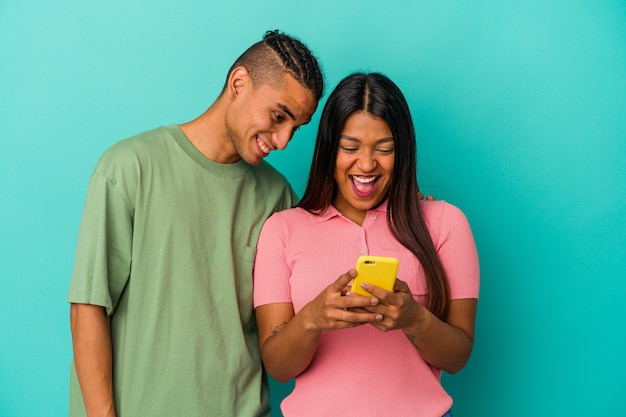 Young latin couple with a mobile phone isolated on blue background