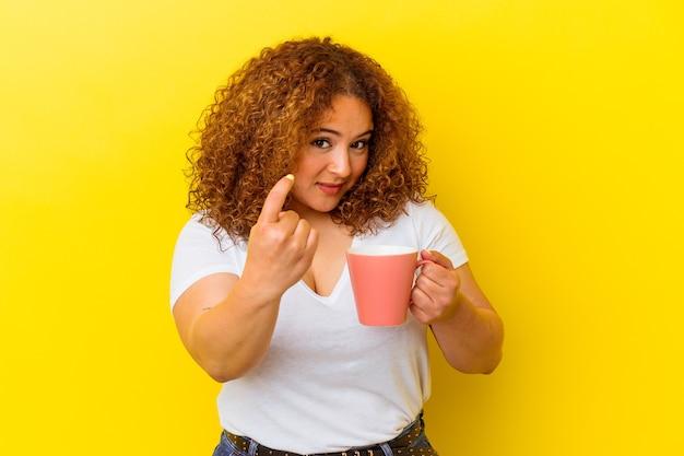 黄色の背景に分離されたカップを保持している若いラテンの曲線美の女性が、近づいてくるように指で指を指しています。
