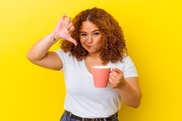 嫌いなジェスチャーを示す黄色の背景にカップを保持している若いラテンの曲線美の女性は、親指を下に向けます。不一致の概念。