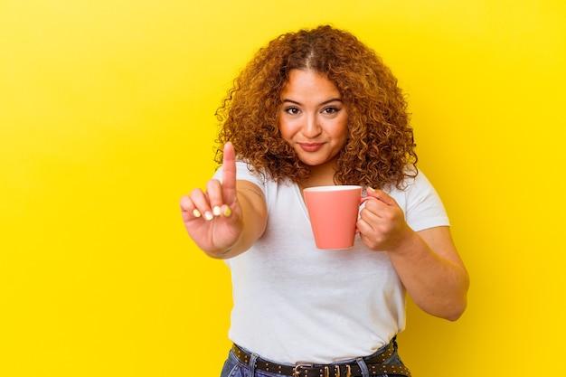 Молодая латинская пышная женщина, держащая чашку, изолированную на желтом фоне, показывает номер один пальцем.