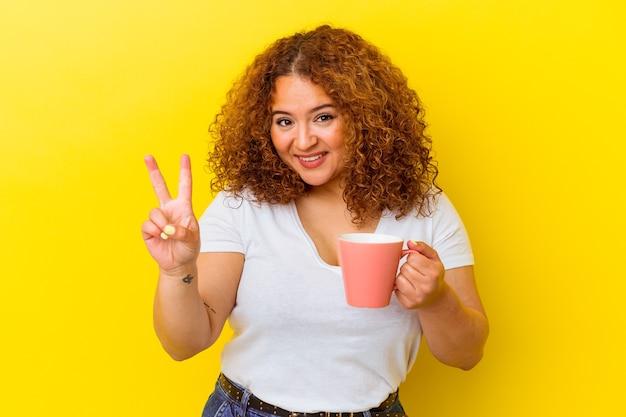 指で 2 番を示す黄色の背景に分離されたカップを保持している若いラテンの曲線美の女性。