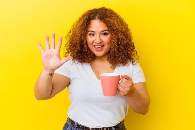 Молодая латинская пышная женщина, держащая чашку, изолирована на желтом фоне, улыбается веселый, показывая номер пять с пальцами.