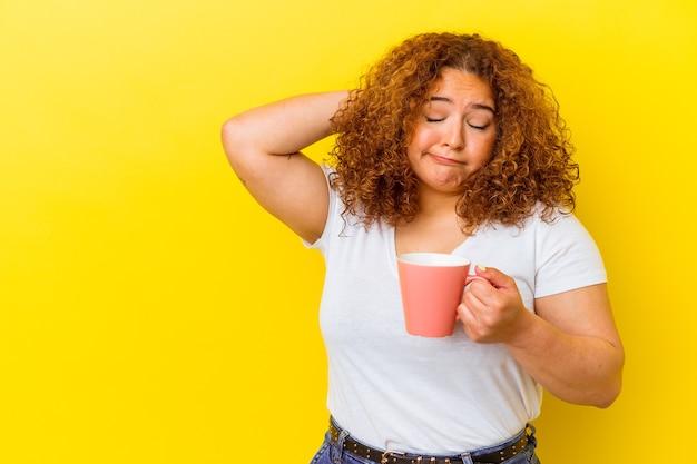 黄色い背景にカップを持ち、頭の後ろに触れ、考え、選択をする若いラテン系の曲線美の女性。