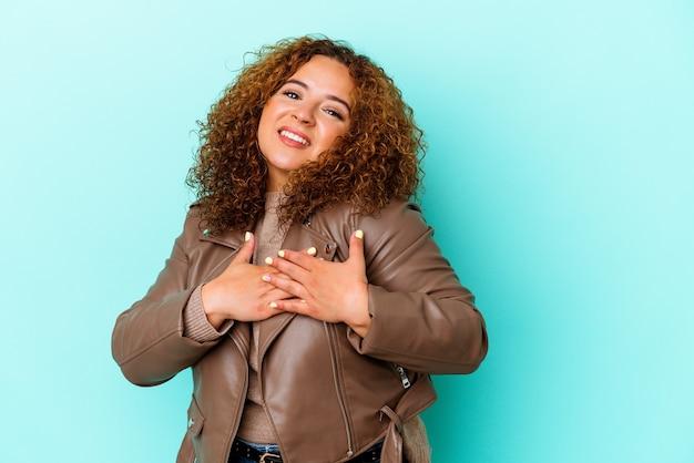 파란색 벽에 고립 된 젊은 라틴 매력적인 여자는 가슴에 손바닥을 눌러 친절식이 있습니다. 사랑 개념.