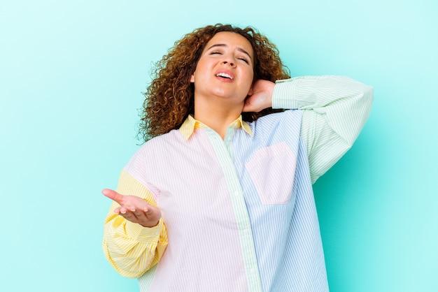 Молодая латинская пышная женщина изолирована на синей стене крича от ярости.