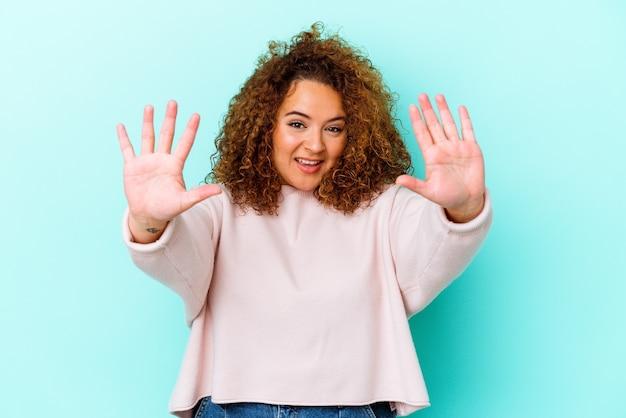 手で10番を示す青い壁に分離された若いラテン曲線の女性。
