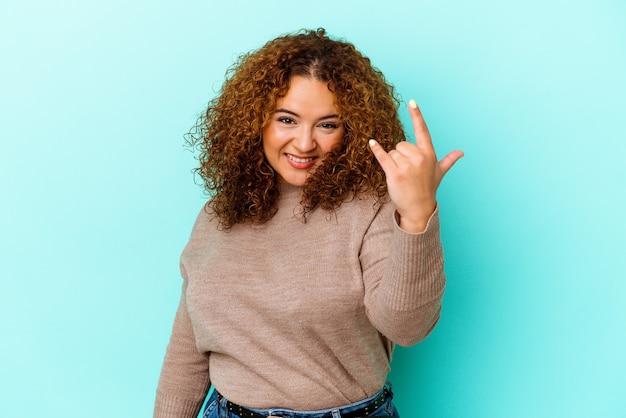 指でロックジェスチャーを示す青い壁に分離された若いラテン曲線の女性
