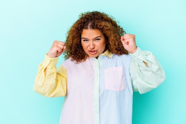 Молодая латинская соблазнительная женщина изолирована на синей стене расстроена криком напряженными руками.
