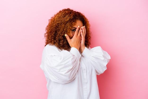 ピンクの壁に隔離された若いラテンの曲線美の女性は、恥ずかしい顔を覆って、指を点滅します。