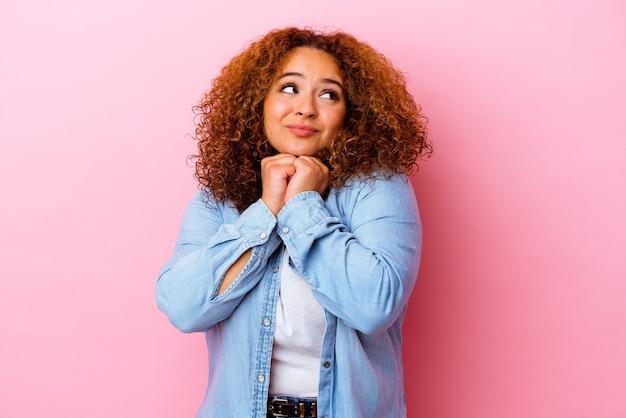 Молодая латинская пышная женщина, изолированная на розовой стене, держит руки под подбородком, счастливо смотрит в сторону.