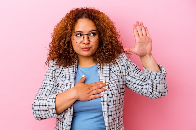 Young latin curvy woman isolated on pink background taking an oath, putting hand on chest.