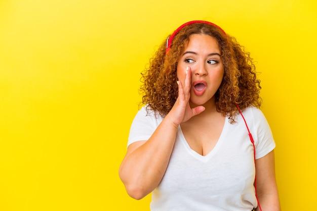 노란색 배경에 고립 된 젊은 라틴 매력적인 여자 듣기 음악은 비밀 뜨거운 제동 뉴스를 말하고 옆으로 찾고