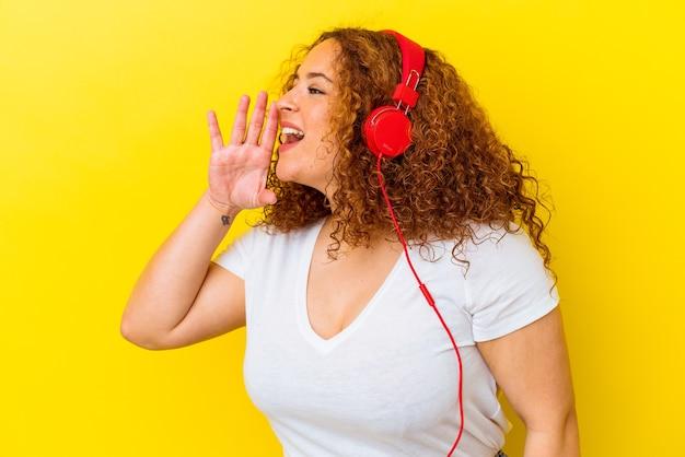 Молодая латинская пышная женщина, слушающая музыку на желтом фоне, кричит и держит ладонь возле открытого рта.