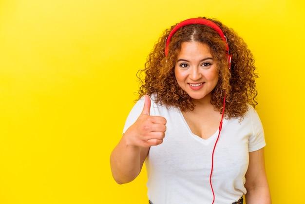 Молодая латинская фигуристая женщина слушает музыку на желтом фоне, улыбаясь и поднимая палец вверх
