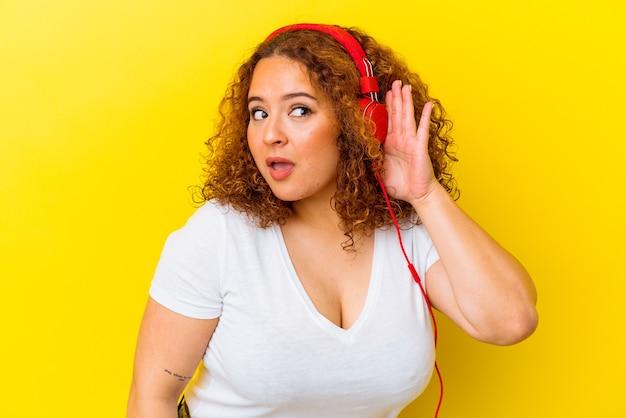 ゴシップを聴こうとしている黄色の壁に分離された音楽を聞いている若いラテン曲がりくねった女性