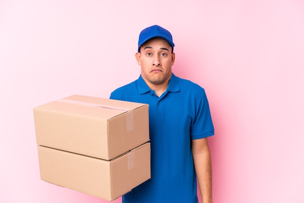 Young latin delivery man isolated shrugs shoulders and open eyes confused.