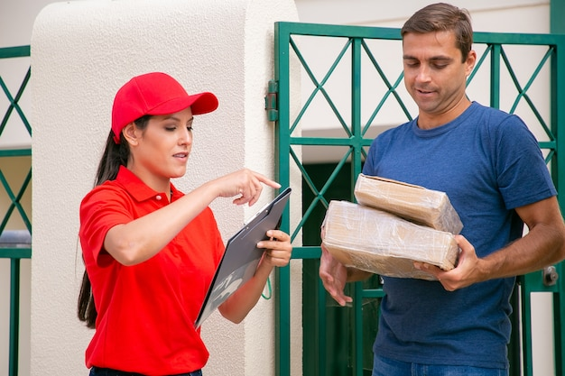 Young latin deliverywoman standing near customer with clipboard. handsome middle-aged caucasian client standing on street and receiving order or cardboard boxes. express delivery and post concept