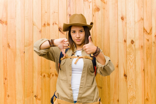 Young latin explorer woman against wooden wall background