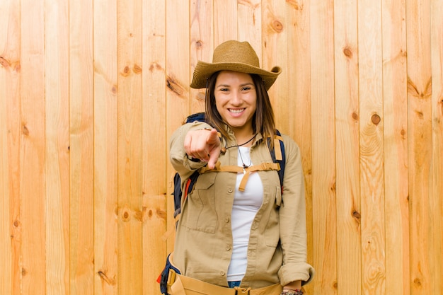 Young latin explorer woman against wooden wall wall