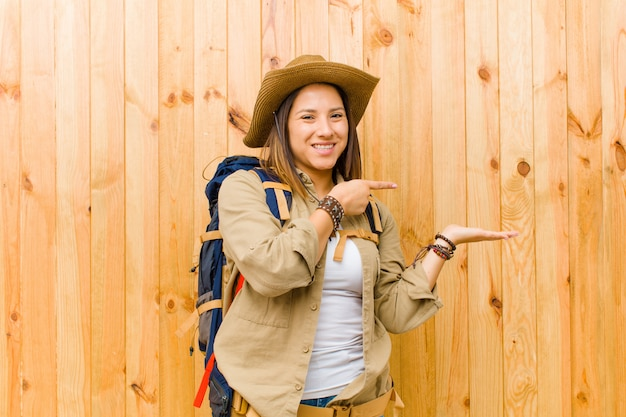 Young latin explorer woman against wooden wall