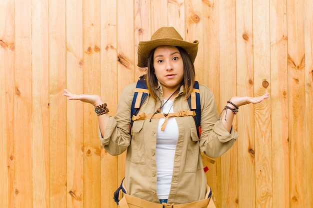 Young latin explorer woman  wooden wall