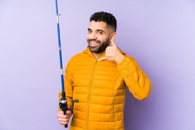 分離されたロッドを保持している若いラテン漁師指で携帯電話のジェスチャーを示す分離されたバスケットを再生若いラテン男