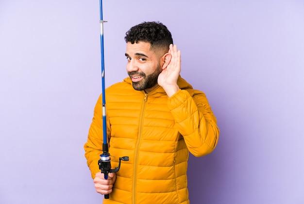 棒を持っている若いラテンの漁師